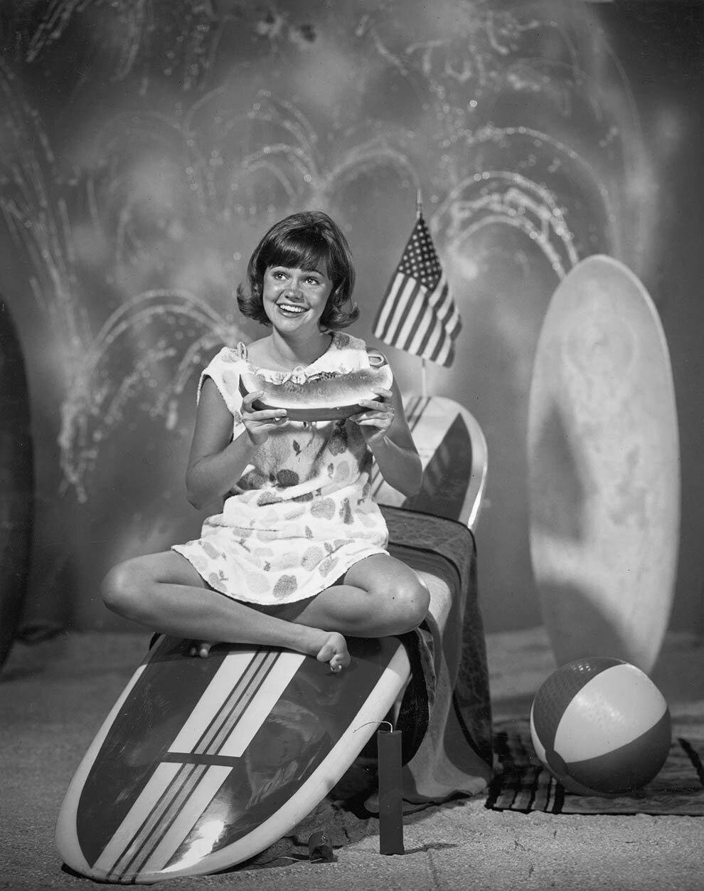 1965.Салли Филд ест арбуз на доске для серфинга.
