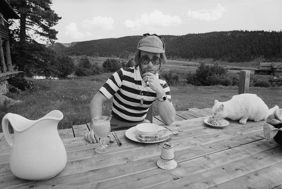 1974. Элтон Джон обедает на свежем воздухе со своим котом. Ранчо Карибу, штат Колорадо