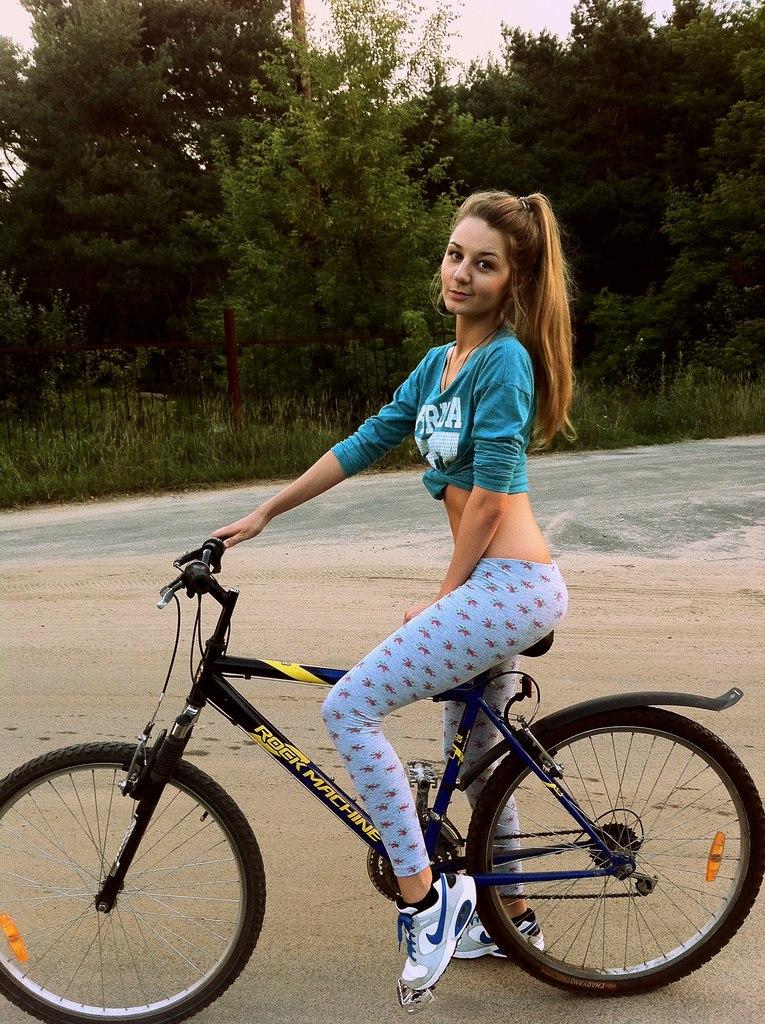 Девчонка  в белых леггинсах на велосипеде