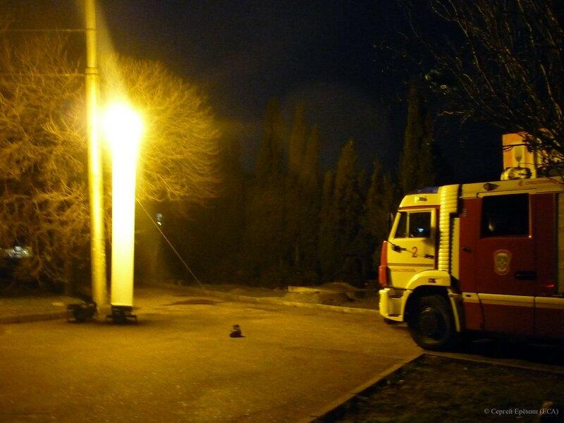 Световой столб вечером около памятника матросу Кошке