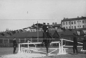 Вид части полигона во время конных состязаний офицер на лошади берет барьер.