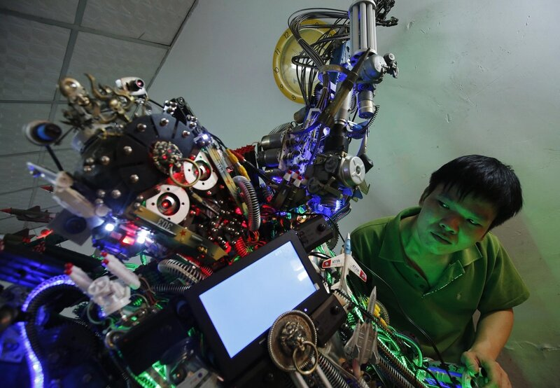 Chinese inventor Tao checks his self-made humanoid robot during a demonstration at his house in Beijing