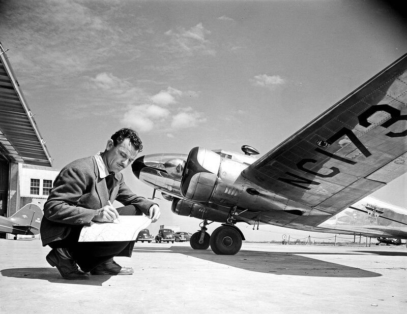A man charting a flight path on a map, while next to a Lockheed Model 12A Electra Junior belonging to Byrd-Frost, Incorporated, at Dallas Love Field Airport. March 1940