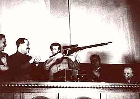 Сталин держит винтовку с прицелом. Прицелился в зал на 17-ый съезд партии ВКП(б).Рядом с ним Каганович и Ворошилов.
