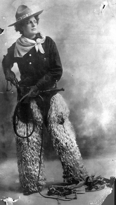 Adele Voughle cowgirl. Studio portrait of a woman in cowpuncher's costume, outfit includes woolies (chaps), a bull whip, pistol, bandana, bridle, and wide brimmed hat with Montana peak. between 1880 and 1900