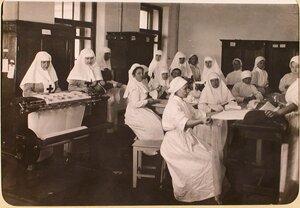 Сестры милосердия госпиталя, оборудованного в здании Политехнического института, за изготовлением перевязочных материалов из марли.
