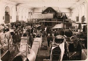Механики и солдаты авиароты за работой в сборочной мастерской.