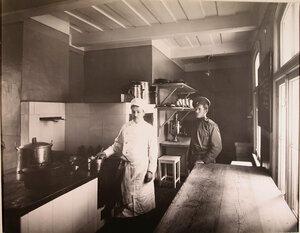 Повар и помощник на кухне патроната-убежища.