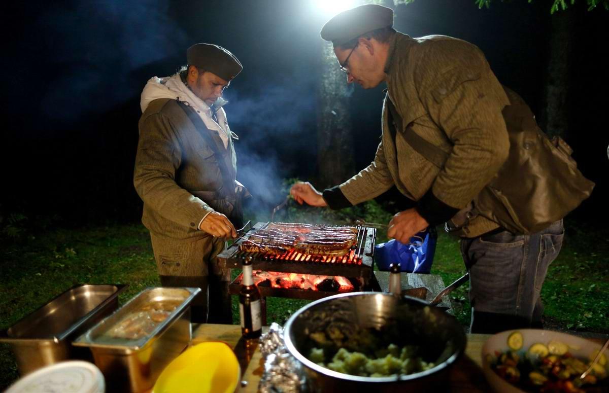 Мужчины из числа гостей в форме солдат Национальной народной армии ГДР, занятые приготовлением ужина