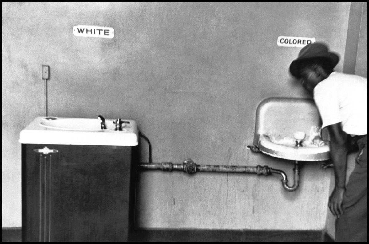 Афро-американец у питьевых фонтанчиков с надписями Для белых и Для цветных