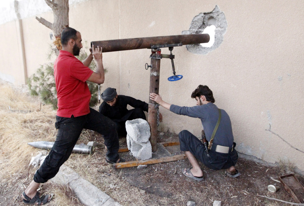 Free Syrian Army fighters prepare to fire rockets towards forces loyal to Syria's president Bashar al-Assad  in Raqqa, eastern Syria