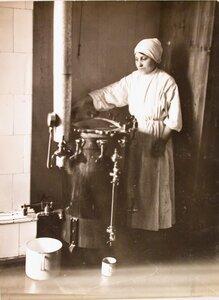Медицинская сестра наливает кипячёную воду из титана в кружку с помощью специального приспособления.