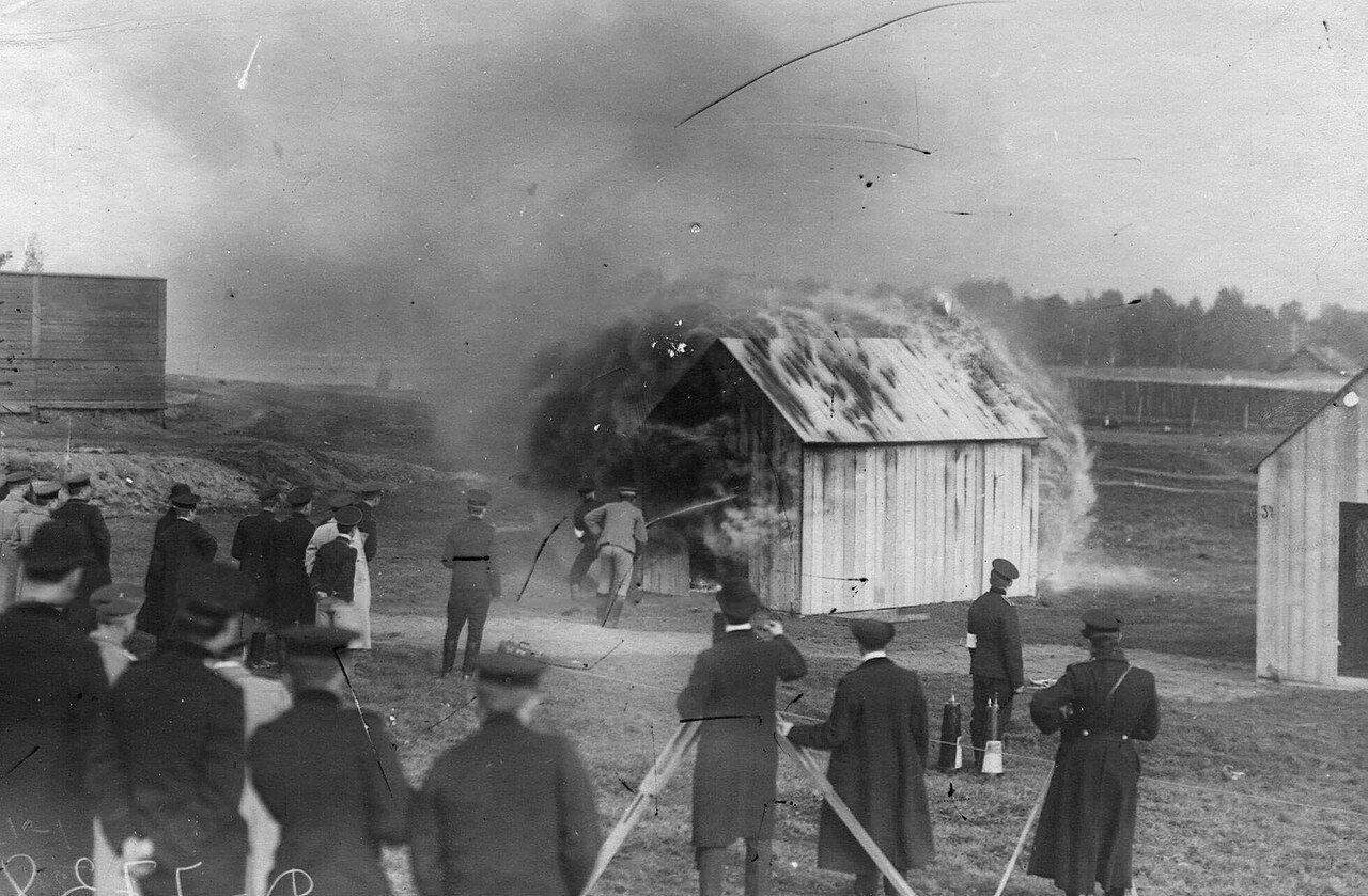 14. Пожарный тушит огнетушителем горящее здание во время испытания огнетушителей новых систем