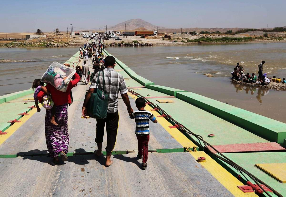 Беженцы переходят ирако-сирийскую границу по понтонному мосту через реку Тигр - вид с иракского берега