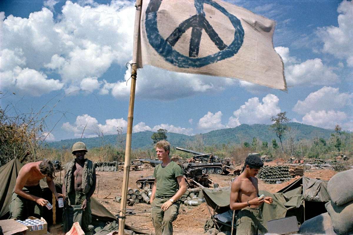 Американские артиллеристы, которые поддерживали своим огнем южновьетнамские войска, действовавшие на территории Лаоса, отдыхают под самодельным пацифистским флагом возле лаосской границы