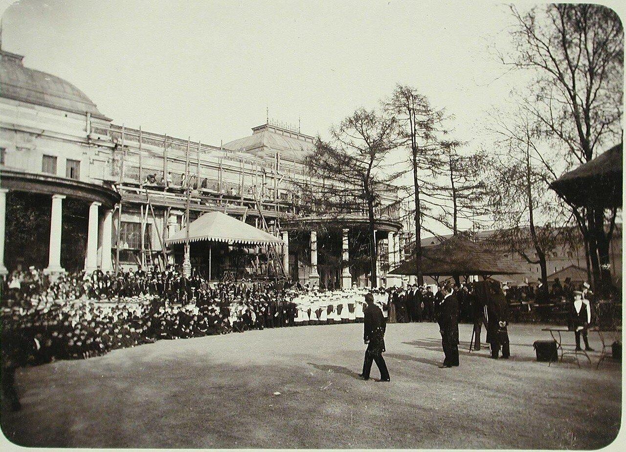 18. Фотограф фотографирует участников празднования юбилея Общества у строящегося здания Народного дома императора Николая II