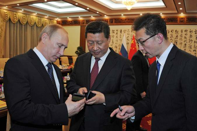 Russia's President Vladimir Putin (L) presents a Russian-produced smartphone YotaPhone-2 to Chinese President Xi Jinping (C) at their meeting in Beijing, November 9, 2014. REUTERS/Mikhail Klimentyev/RIA Novosti/Kremlin (CHINA  - Tags: BUSINESS POLITICS) T