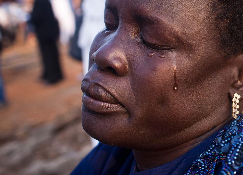 18. Слезы счастья на лице у женщины, которая стоит у только что открытой статуи доктора Джона Гаранг