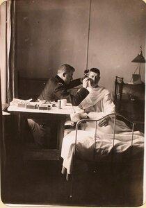 Студенты Политехнического института бреет раненого солдата в одной из палат госпиталя, оборудованного в здании института.
