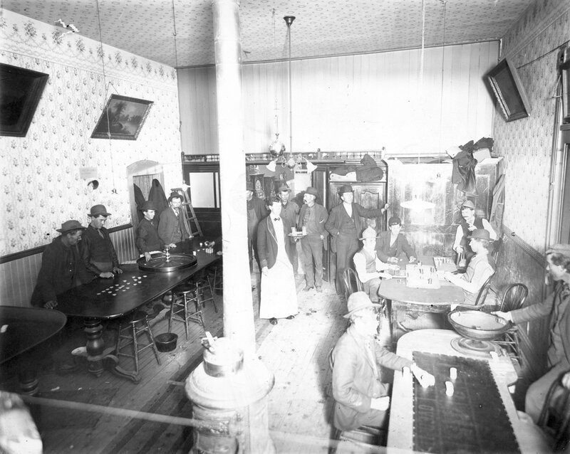 Interior view of a saloon in Leadville (Lake County), Colorado; shows men gambling with poker chips, a roulette wheel, and slot machines; between 1880 and 1910.
