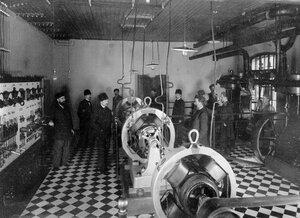 Группа служащих склада в машинном отделении наблюдают за включением динамомашины.