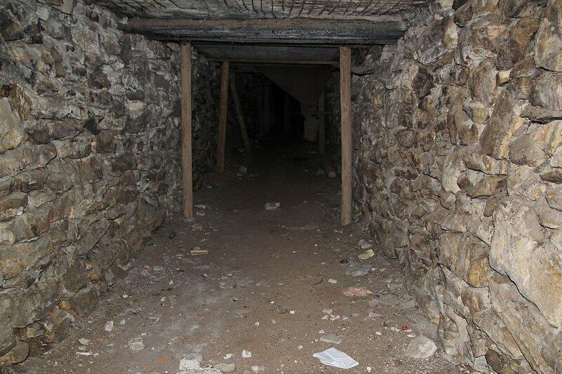 Подземный ход со стенами из натурального камня под башней заброшенного элеватора хлебоприёмного предприятия в пос. Медведок