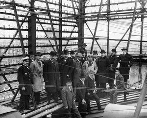 Чиновники управления связи и сотрудники городской телефонной станции осматривают установленное на крыше оборудование.