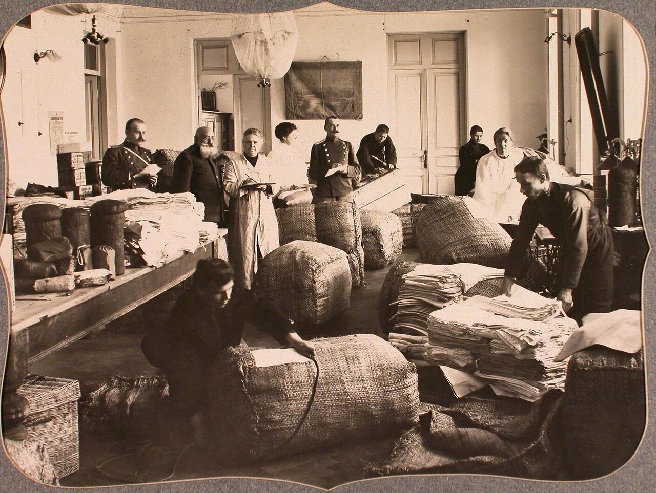22. Работники и представители Красного Креста за упаковкой вещей для отправки в действующую армию в одном из помещений общины