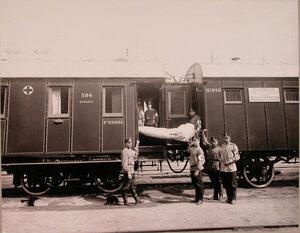 Группа санитаров поезда с носилками у специально оборудованной открытой для вноса тяжелораненых площадки.