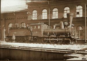 Группа железнодорожных служащих на платформе паровоза.