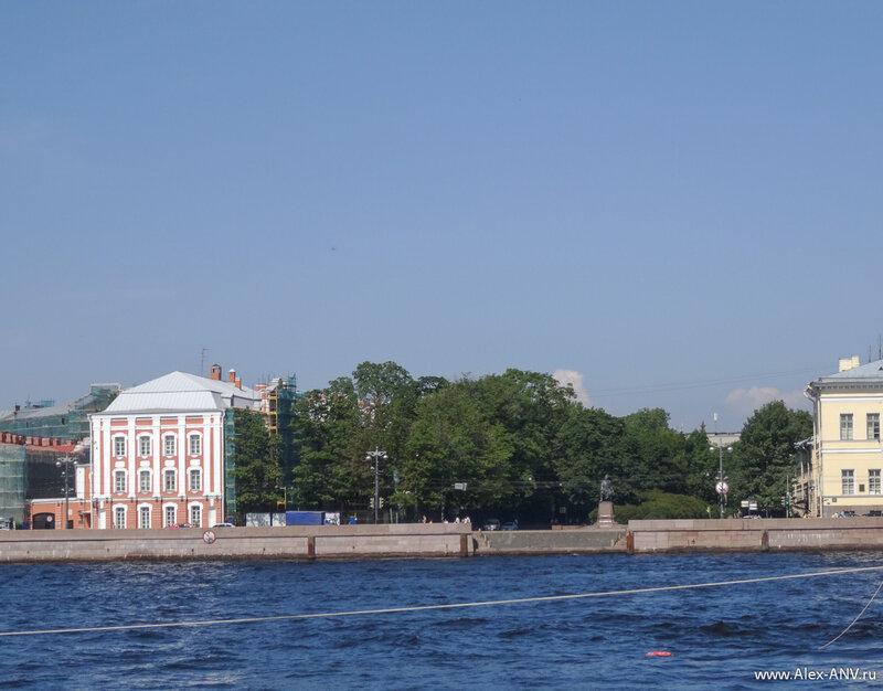 НА противоположном берегу в стройном ряду зданий ярко выделяется зелёное пятно - Менделеевская линия.
