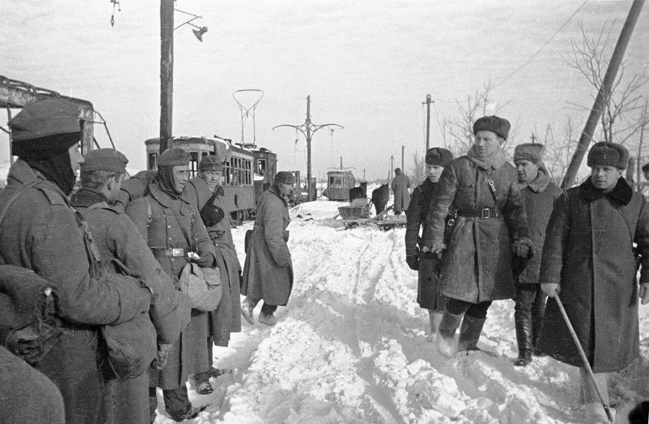 1943. Советские офицеры проходят мимо немецких пленных, стоящих у разбитых трамвайных вагонов в Сталинграде. Второй справа — командующий 62-й армией генерал-лейтенант В.И. Чуйков.