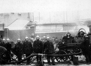 Группа пожарных у машины на Большой Дворянской улице во время тушения пожара в соборе Пресвятой Троицы.
