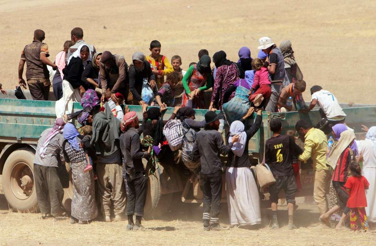 Группа беженцев загружается в грузовой автомобиль для облегчения своего пути в сторону границы