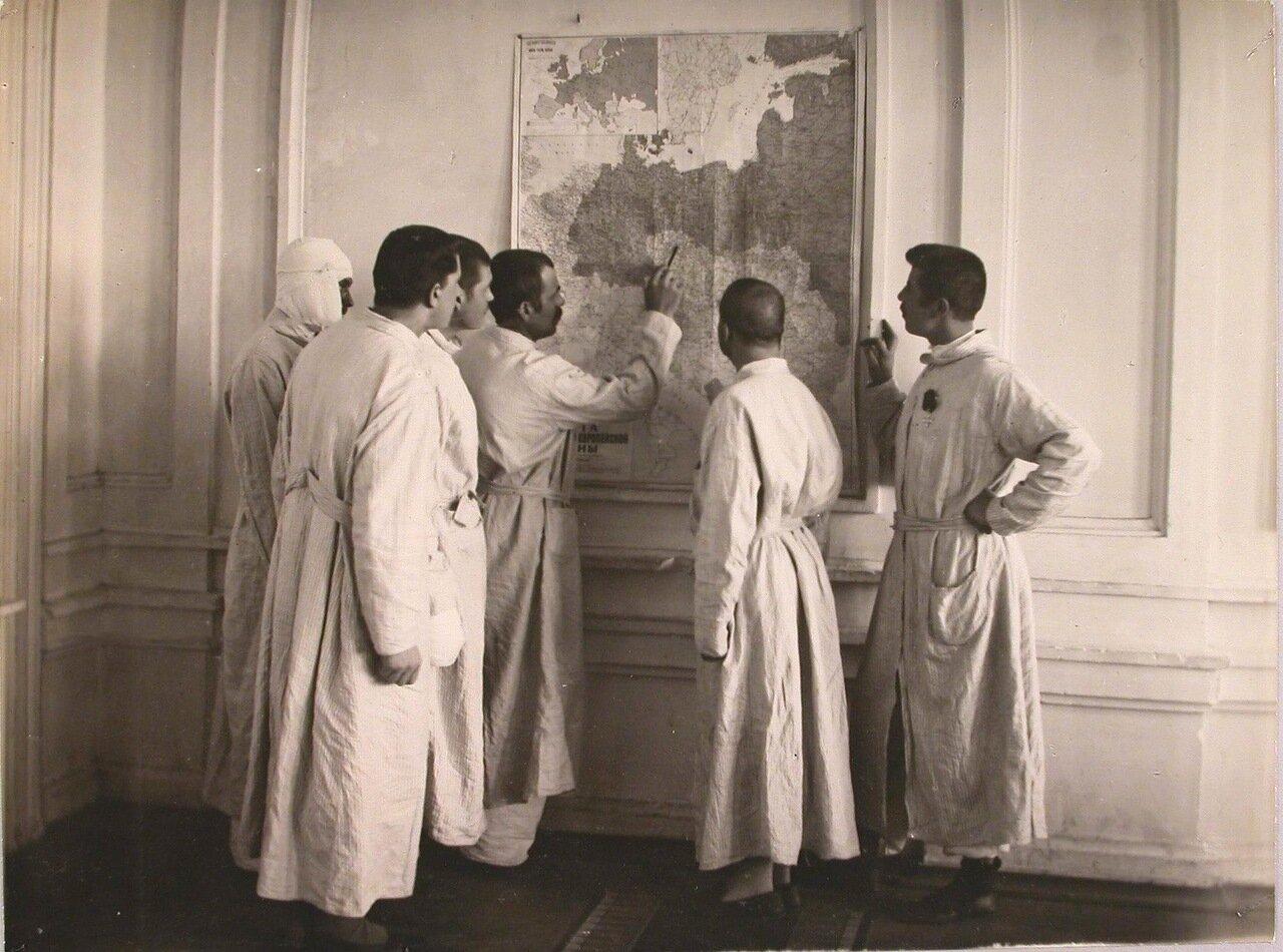 24. Группа раненых у карты военных действий в коридоре госпиталя