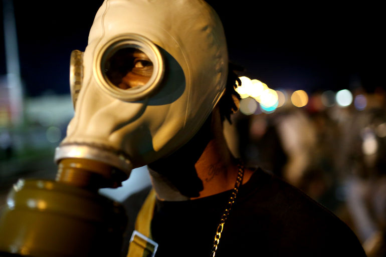 FERGUSON, MO - AUGUST 18: A demonstrator protesting the shooting death of Michael Brown wears a gas mask on August 18, 2014 in Ferguson, Missouri. Protesters have been vocal asking for justice in the shooting death of Michael Brown by a Ferguson police of