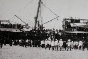 Военные чины, горожане встречают на пристани в порту спускающихся с трапа  парохода   Петербург эвакуируемых нижних чинов и запасных( прибывших с Дальнего Востока).