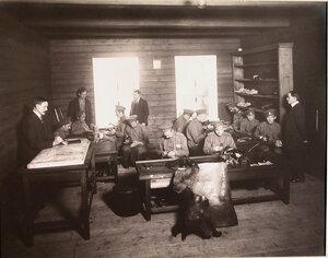 Группа нижних чинов, призреваемых в убежище, за работой в летней сапожной мастерской.