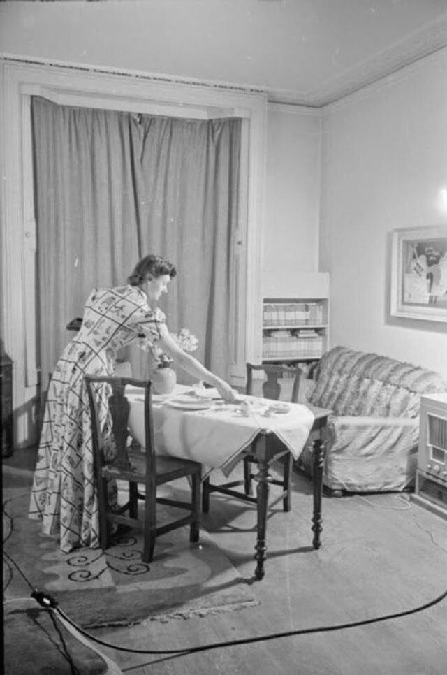 25. Оливия сервирует стол к ужину в гостиной. Она ждет своего мужа лейтенанта Кеннета Дэй. Он должен приехать домой в отпуск, поэтому стол накрыт на двоих и украшен вазой с цветами