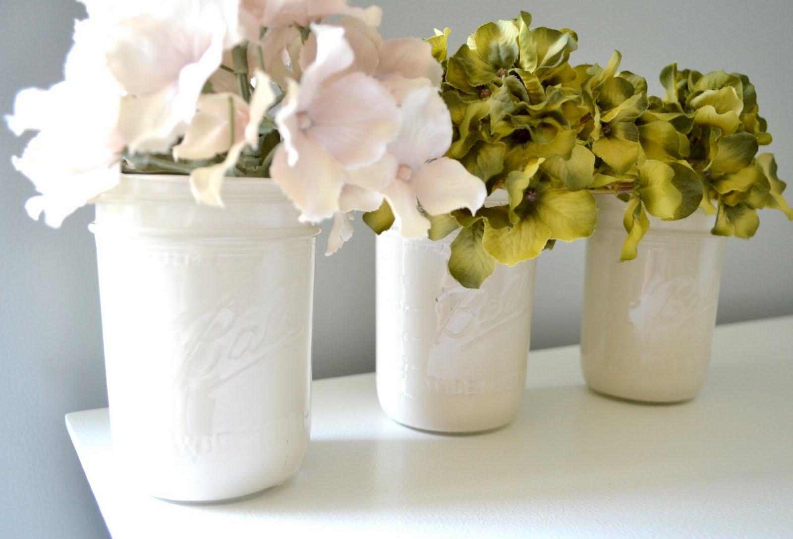 белые банки с цветами на белом столе