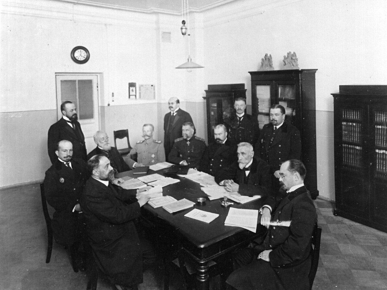 19. Группа преподавателей за столом в учительской комнате