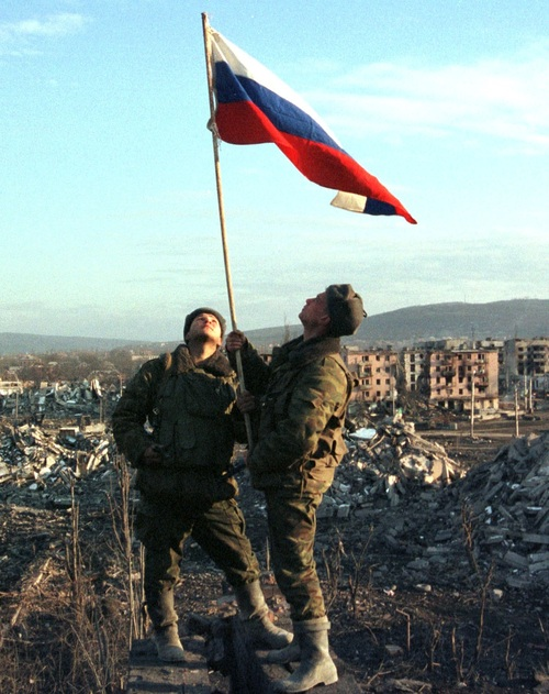Russian soldiers stand with a raised flag after a mopping up operation in the remains of the Chechen..