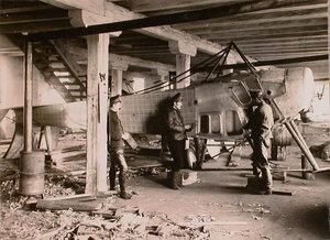 Группа техников отряда за ремонтом летательного аппарата в мастерской г. Терещенко.