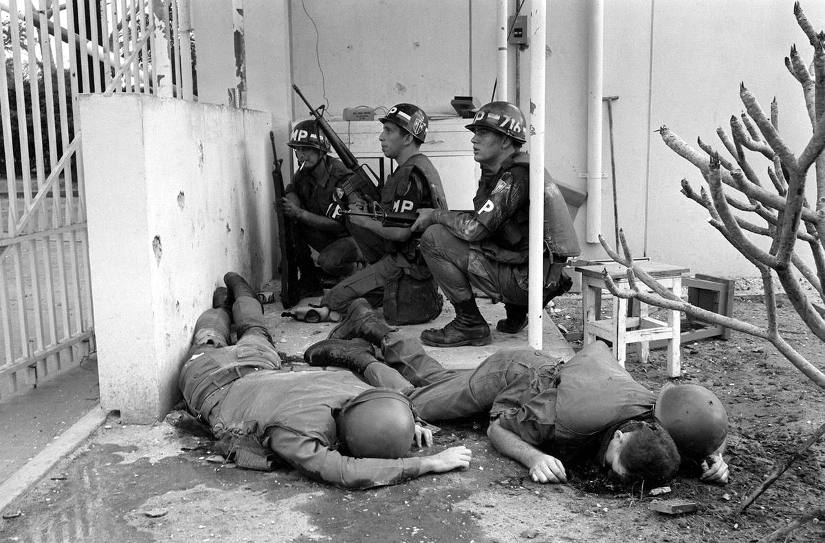 Мертвые американские солдаты и военные полицейские, которые укрываются за стеной у входа в посольства США в Сайгоне, пострадавшее в результате нападения вьетнамских партизан (31 января 1968 года)