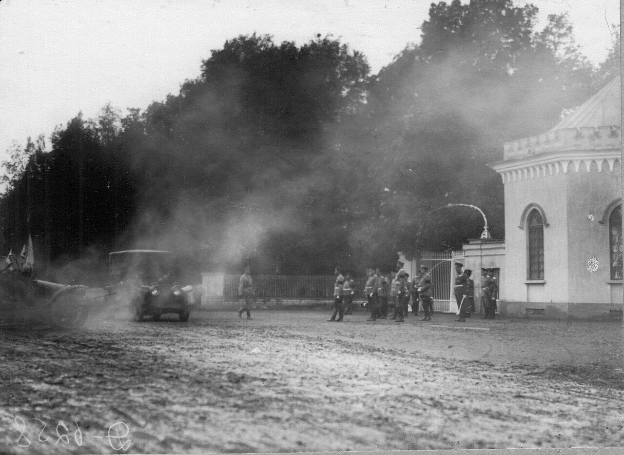 14. Император Николай II и сопровождающие его лица у ворот парка следят за проходящими мимо них автомобилями