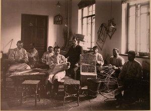 Группа призреваемых за изготовлением плетеных изделий в мастерской.