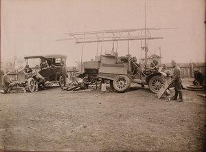Механики за ремонтом автомобиля Оверленд II корпусного авиационного отряда и автомобиля-мастерской Заурер IV корпусного авиационного отряда.