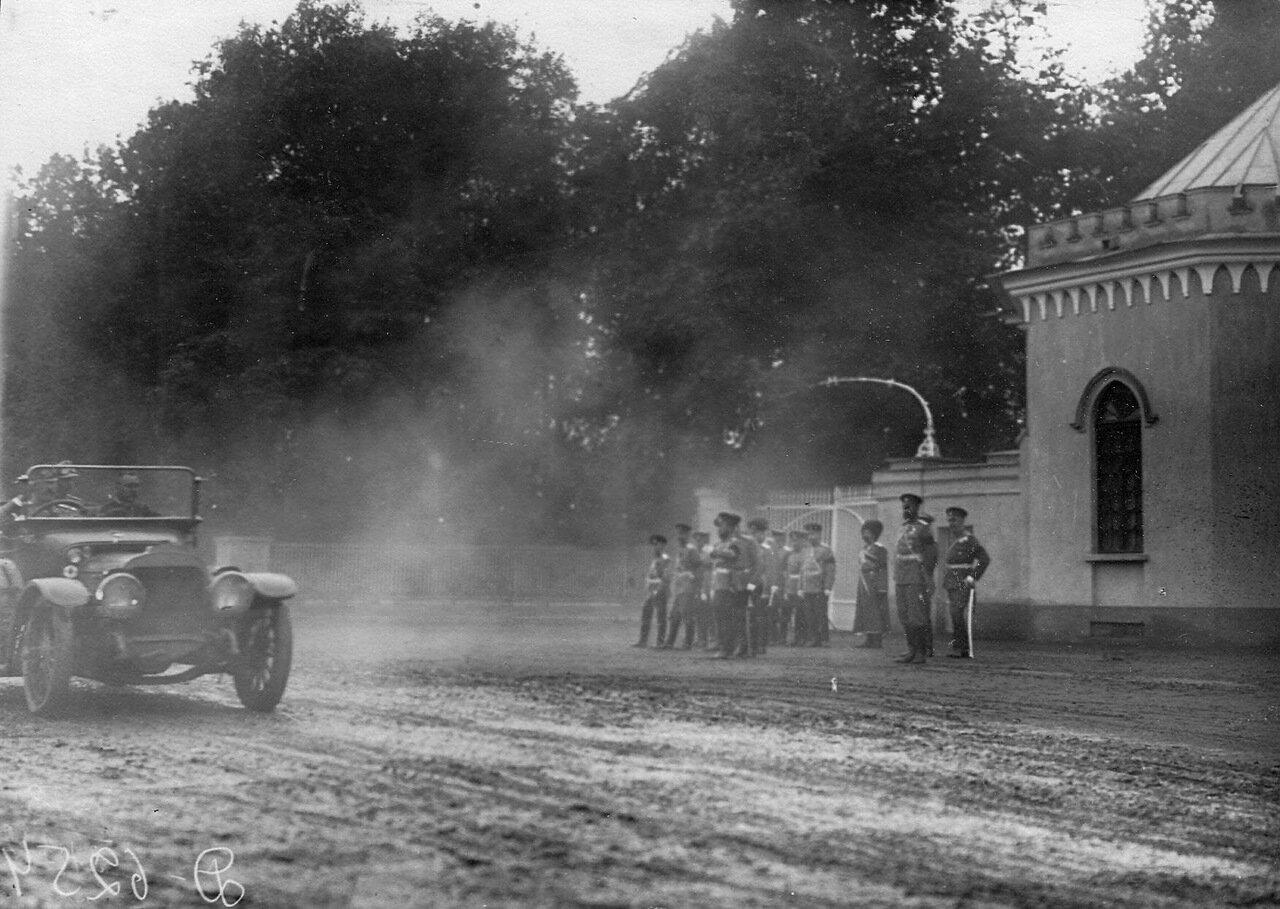 13.Император Николай II и сопровождающие его лица у ворот парка следят за проходящими мимо них автомобилями