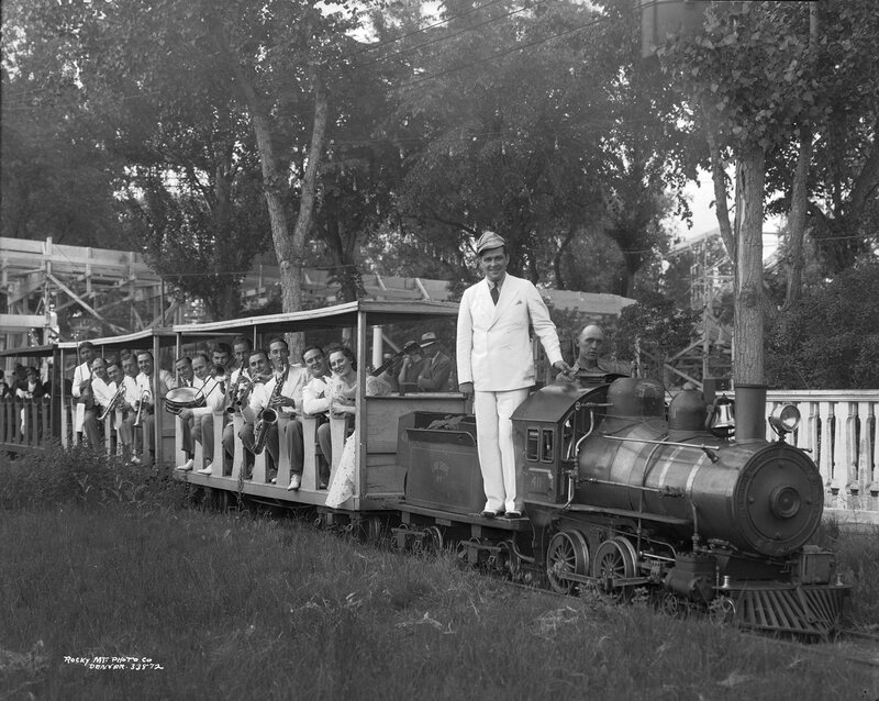 Jimmy Garrigan stands on a miniature locomotive at Lakeside Amusement Park in Lakeside (Jefferson County), Colorado, 1934 June 27.