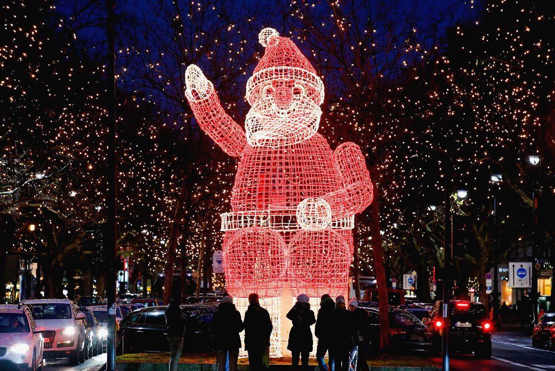 Люди идут по Рождественской ярмарке в Эрфурте, Германия. (Фото: Jens Meyer)